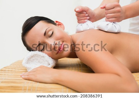 Beautiful brunette enjoying a herbal compress massage in the health spa