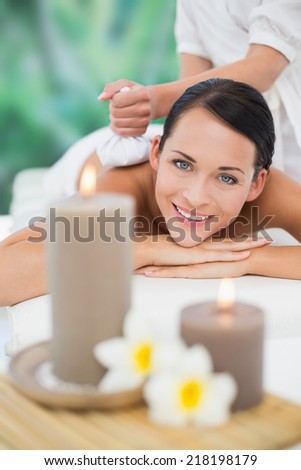 Beautiful brunette enjoying a herbal compress massage smiling at camera at a luxury spa - stock photo