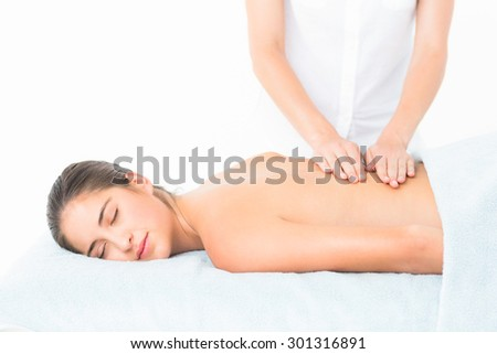 Beautiful brunette enjoying a massage at the health spa - stock photo
