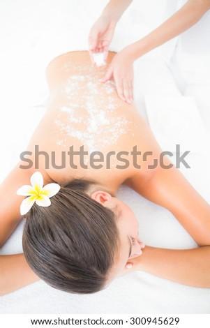 Beautiful brunette enjoying a salt scrub treatment at the health spa - stock photo