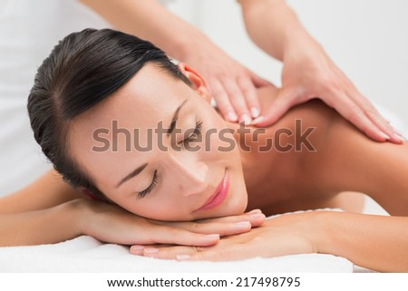 Beautiful brunette enjoying a shoulder massage in the health spa - stock photo