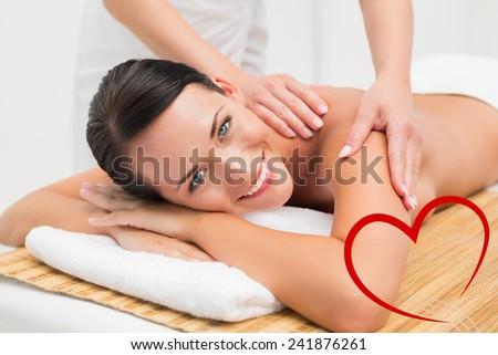 Beautiful brunette enjoying a shoulder massage smiling at camera against heart - stock photo