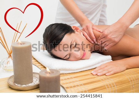 Beautiful brunette enjoying a shoulder massage smiling at camera against heart - stock photo