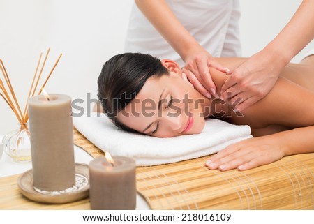 Beautiful brunette enjoying a shoulder massage smiling at camera in the health spa - stock photo