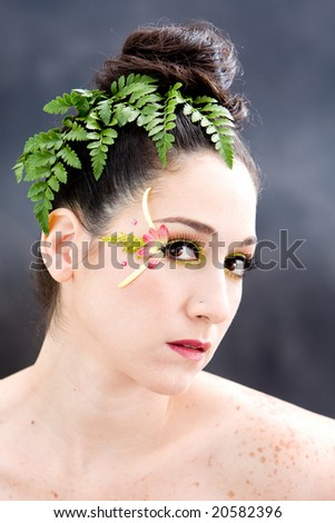 Beautiful brunette face with pink green yellow eye flower petal makeup, isolated on gray - stock photo