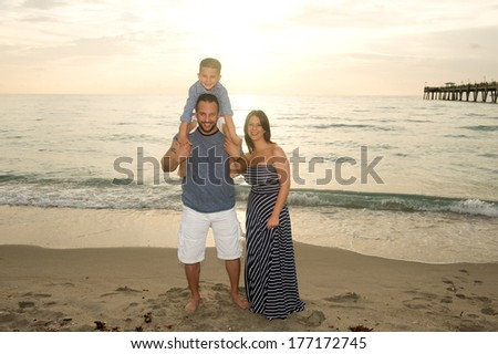 Beautiful brunette family smiling at the beach at sunrise - stock photo