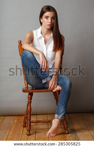 beautiful brunette fashion model posing at studio, sitting on chair - stock photo