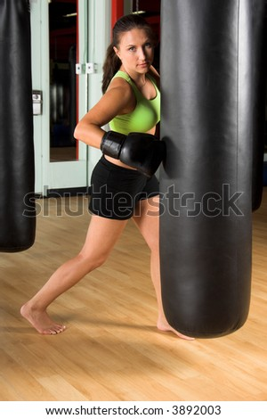 Beautiful brunette female boxer working out punching on the heavy bag.