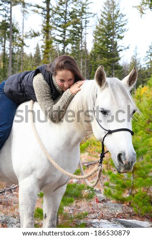 Beautiful brunette female spending time with her white horse - stock photo