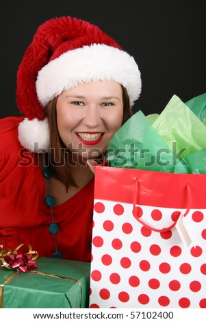 Beautiful brunette female with christmas gifts wearing a fluffy hat