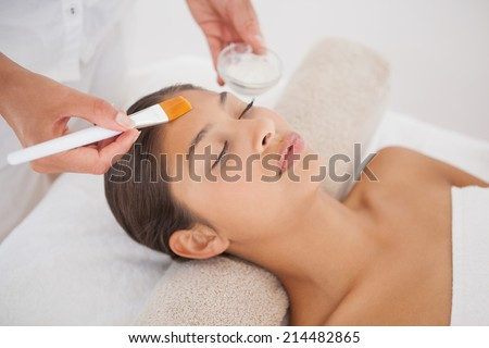 Beautiful brunette getting a facial at the health spa - stock photo