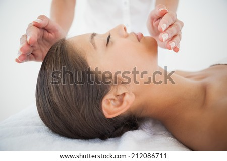 Beautiful brunette getting reiki therapy at the health spa - stock photo