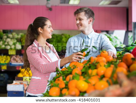 Beautiful brunette girl and boyfriend buying citruses in grocery store