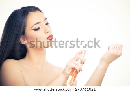 Beautiful brunette girl applying perfume on her hand - stock photo