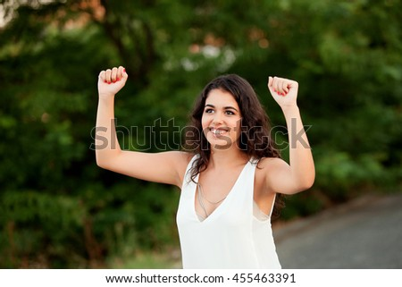 Beautiful brunette girl celebrating something in the park wiht many plants of background - stock photo