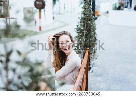 beautiful brunette girl cute smiling sitting on a Park bench - stock photo