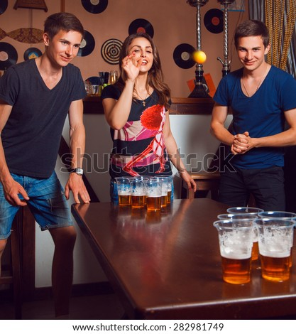 Beautiful brunette girl having fun with twins playing beer pong. Square photo - stock photo