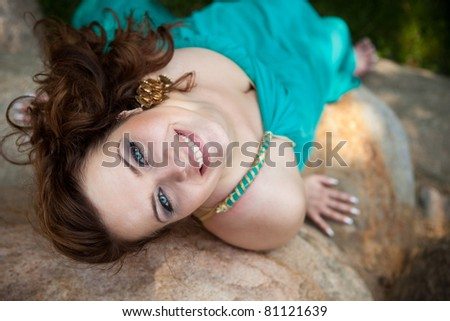 Beautiful brunette girl in a blue dress lying on a rock - stock photo