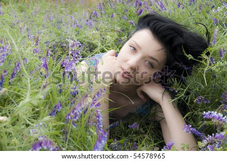 Beautiful Brunette Girl in a field of blue flowers - stock photo