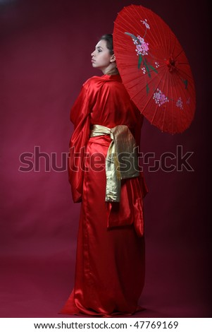 Beautiful brunette girl in a japanese kimono with umbrella - stock photo