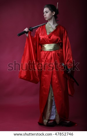 Beautiful brunette girl in a red kimono with a katana - stock photo