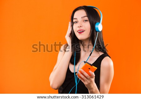 Beautiful brunette girl, in black blouse, listening to music with big blue headphones and holding smart phone in her hand - isolated on orange background, in studio, waist up - stock photo