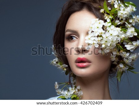 Beautiful brunette girl in blue dress with a gentle romantic make-up, pink lips and flowers. The beauty of the face. Portrait shot in the studio.