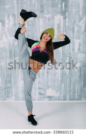 Beautiful brunette girl in funny knitted green hat and casual clothes stay in gymnastic pose, smile and show thumbs up. Slim gymnast posing. Balance posing - stock photo