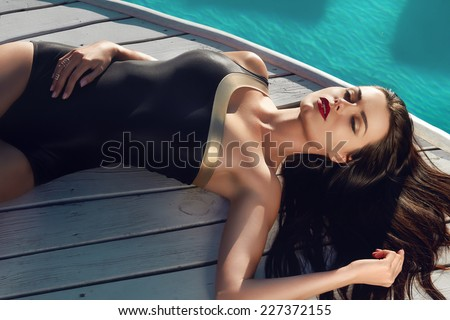 Beautiful brunette girl in good shape with long dark hair and tan skin red lips in black swimming suite with golden line with modern rings lie near the pool with green water closing her eyes and smile - stock photo