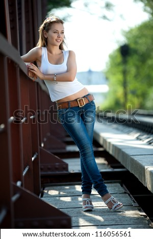 Beautiful brunette girl in jeans and a t-shirt posing on railroad tracks