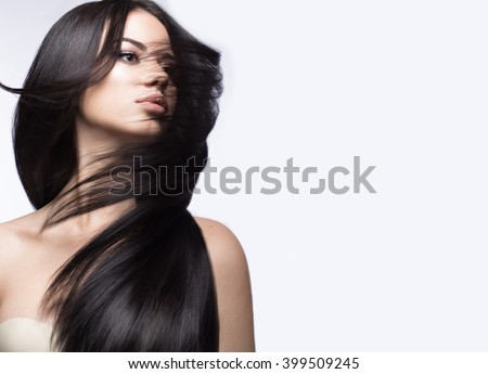 Beautiful brunette girl in move with a perfectly smooth hair, and classic make-up. Beauty face.  - stock photo