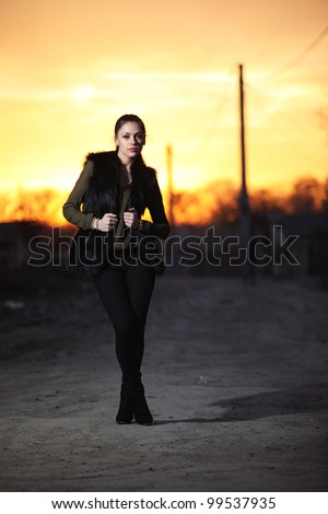 Beautiful brunette girl in street at sunset