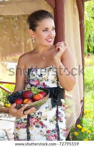 Beautiful brunette girl in the garden. The girl is holding a fruit