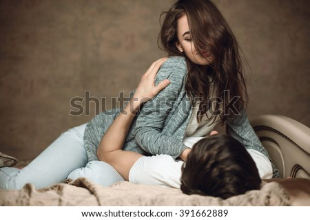 beautiful brunette girl lies on top on guy on the bed - stock photo