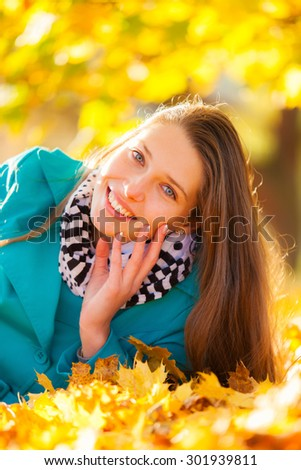 Beautiful brunette girl lying in autumn leaves with smilling face. Concept of happiness and joy