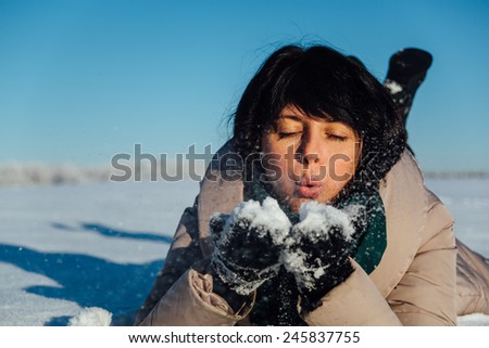 Beautiful brunette girl lying on the snow and blows snow from hands