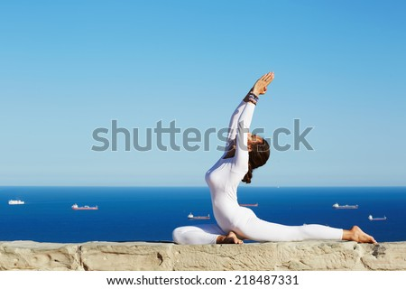 Beautiful brunette girl makes yoga pose on high altitude with sea and sky horizon on background, seated in one of yoga pose young woman with perfect body engage yoga meditation outdoors - stock photo