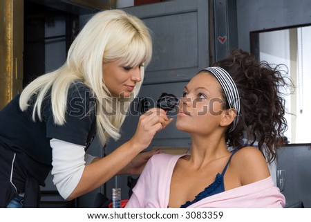 beautiful brunette girl model, while make-up before shooting session (professional make-up artist doing his job) - stock photo