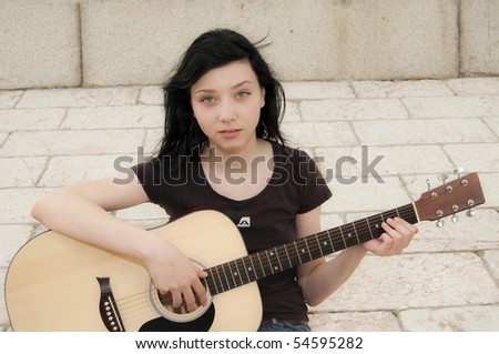 Beautiful Brunette Girl Playing a Guitar on Rocks - stock photo