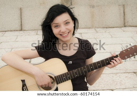 Beautiful Brunette Girl playing guitar - stock photo
