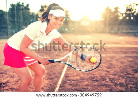 beautiful brunette girl playing tennis with racket, balls and sports equipment. Close up portrait of beautiful woman on tennis court with athletic wear and smiling - stock photo