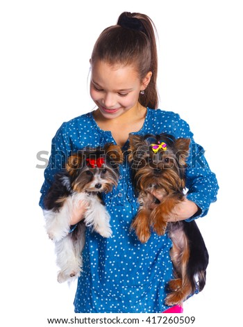 Beautiful brunette girl playing with her two yorkshire terriers. Isolated on the white background