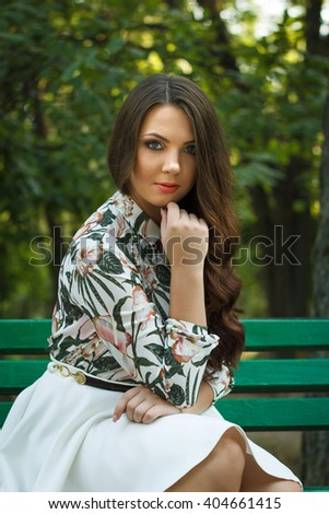 Beautiful brunette girl poses and relaxed on bench outdoors - stock photo
