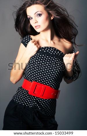 Beautiful  brunette girl posing in studio on dark background - stock photo