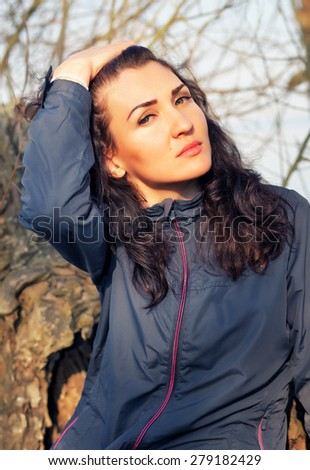 Beautiful brunette girl posing on a nature at the old tree. Leisure and fashion