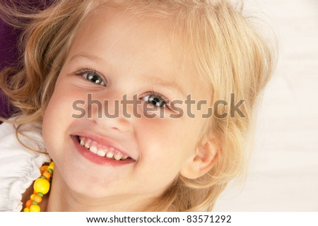 Beautiful brunette girl putting her hands to the face lying on the floor and  looking directly into the camera on white background close-up - stock photo