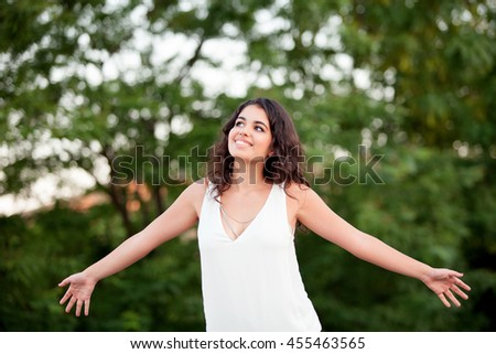 Beautiful brunette girl relaxing in the park with many plants of background - stock photo