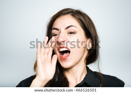 beautiful brunette girl shouting to someone in the distance in the black, isolated on white background