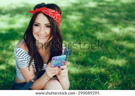 Beautiful brunette girl, sitting on the grass with mobile phone. Wearing red bandana and striped top. Sunny day. Copy space. - stock photo