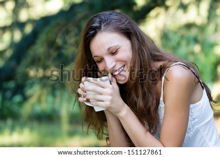 Beautiful Brunette Girl smiles Drinking Tea or Coffee. Woman with a Cup at park. - stock photo